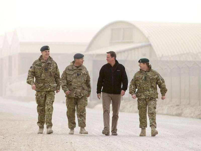 Britain's Prime Minister David Cameron (2nd R) walks through Kandahar airfield with Group Captain Gerry Mayhew (L), Wing Commander Scott Ray (2nd L) and Colonel Jim Morris Military Assistant (R) during a pre-Christmas visit to British forces in Afghanistan. Reuters/Jeff J Mitchell/Pool