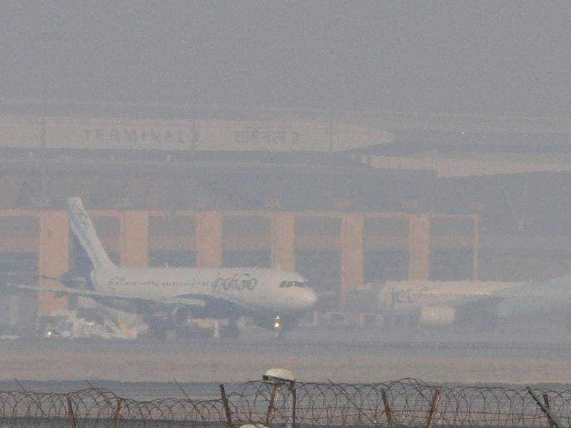 A passenger plane waits to take off as fog begins to clear at the Indira Gandhi International Airport in New Delhi.