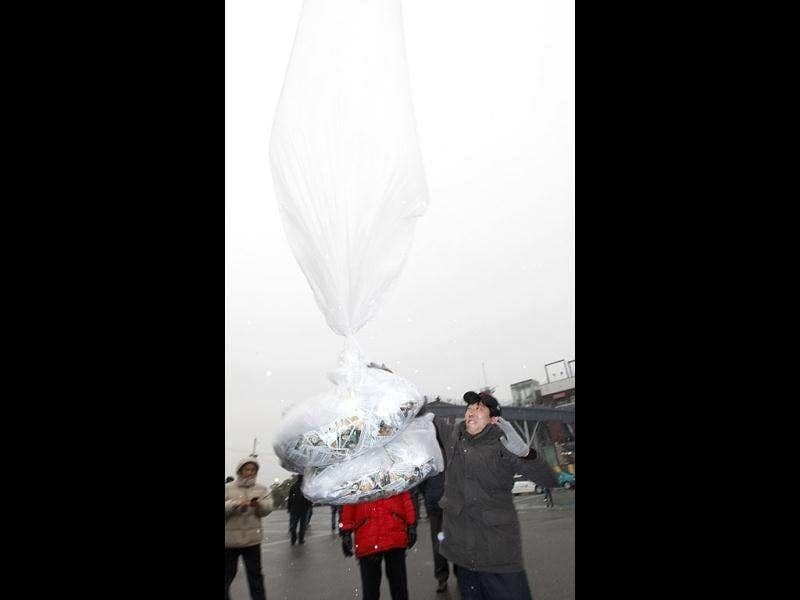 Park Sang-hak (R), a North Korean defector and an anti-North Korea activist living in South Korea, releases balloons carrying anti-North Korea leaflets toward the North at the Imjinkak pavilion, near the demilitarized zone which separates the two Koreas in Paju, about 50 km north of Seoul. Reuters/Kim Kyung-Hoon