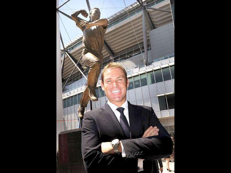 Australian cricketer Shane Warne poses in front of his statue outside the Melbourne Cricket Ground in Melbourne.