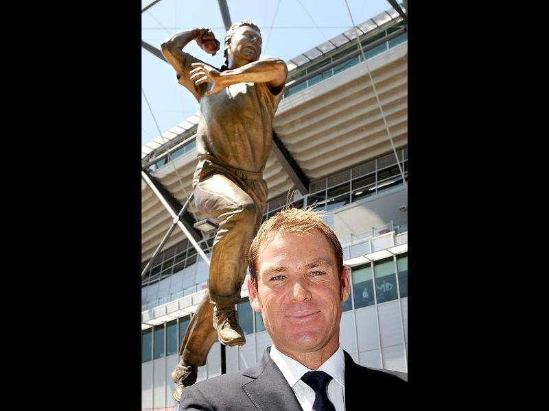 Australian cricketer Shane Warne stands in front his statue unveiled outside the Melbourne Cricket Ground in Melbourne.