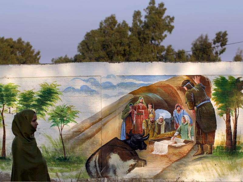 A Christian woman, left, walks by a wall painted with the Nativity scene in preparation for the upcoming Christmas holiday in a Christian neighbourhood of Islamabad, Pakistan. AP Photo