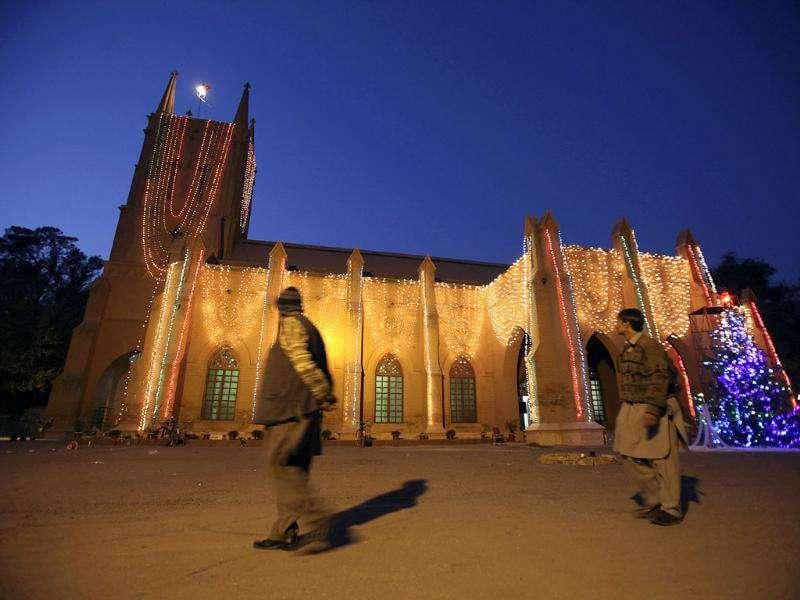 Pakistani Christians walks past St John's Cathedral as it is illuminated with lights ahead of Christmas celebrations in Peshawar, Pakistan. AP Photo