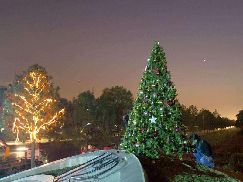 A group of Christian youths give final touches to Christmas trees alongside a main intersection in Islamabad, Pakistan. AP Photo