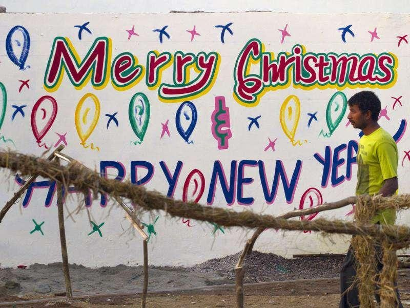 A man walks past a wall painted with Christmas and Happy New year wordings at a Christian neighborhood in Islamabad, Pakistan. AP Photo