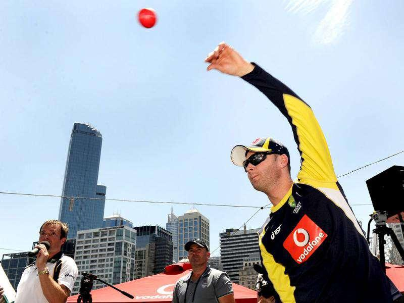 Australian cricket captain Michael Clarke bowls a ball as members of the Indian and Australian teams meet a large crowd at a public event in Melbourne. AFP Photo/William West