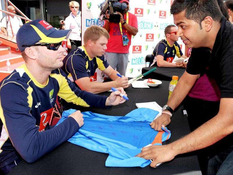 Australian cricket captain Michael Clarke (L) signs autographs for fans as members of the Indian and Australian teams meet the public at an event in Melbourne. AFP Photo/William West