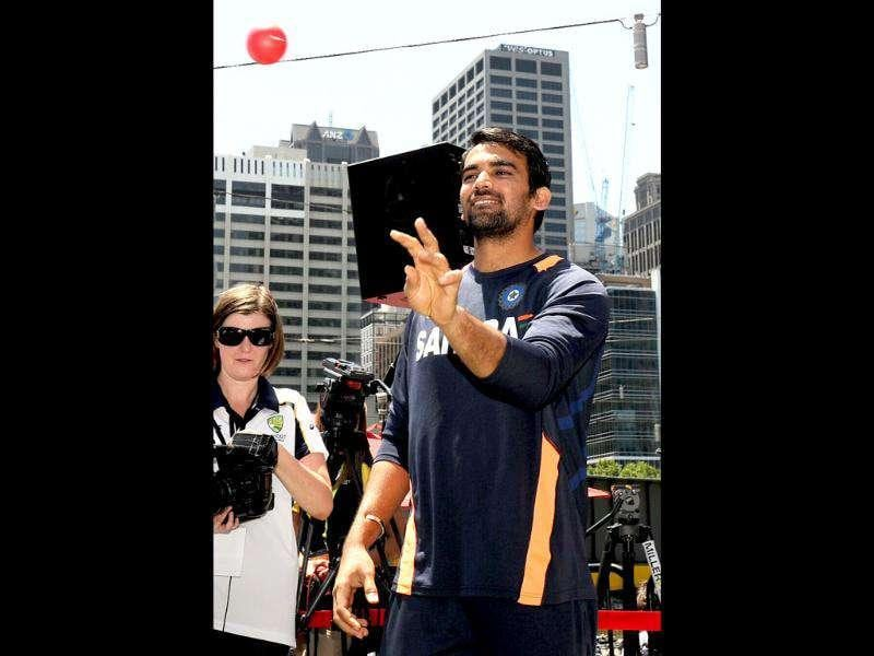 Cricketer Zaheer Khan bowls a ball to a young fan as members of the Indian and Australian teams meet a large crowd at a public event in Melbourne. AFP Photo/William West