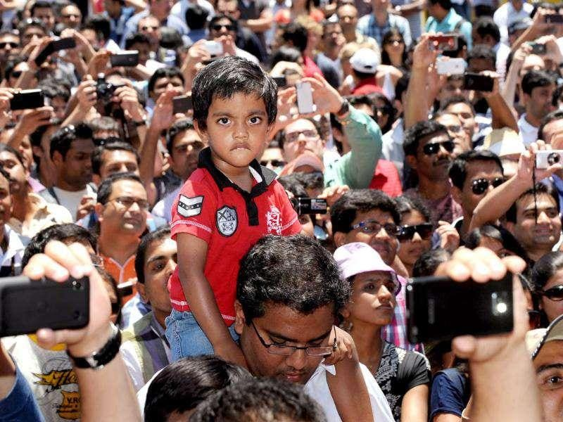 A young fan sits on his father's shoulders as he awaits to gather autographs as members of the Indian and Australian teams meet a large crowd at a public event in Melbourne. AFP Photo/William West
