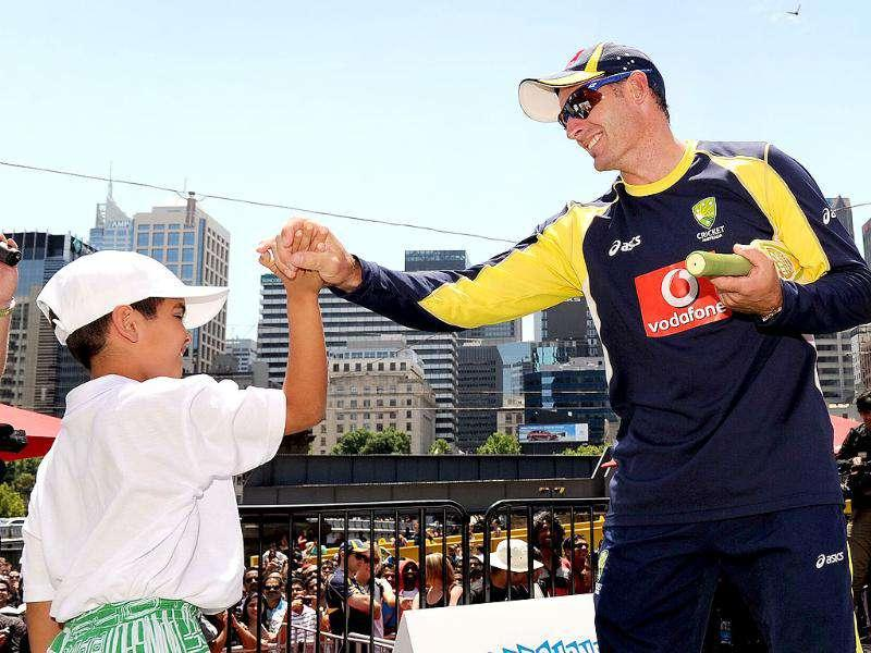 Australian cricketer Michael Hussey (R) high-fives a young fan as members of the Indian and Australian teams meet a large crowd at a public event in Melbourne. AFP Photo/William West