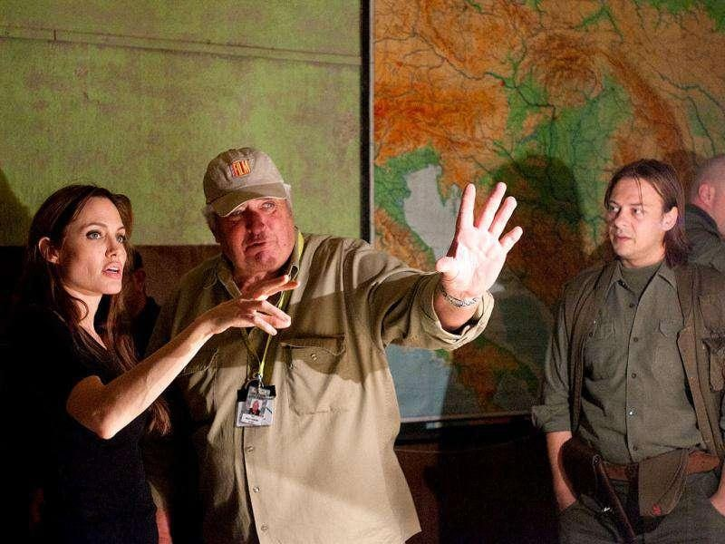 In this image released by Film District, writer-director Angelina Jolie, left, speaks with the director of photography Dean Semler, center, during the filming of In the Land of Blood and Honey. (AP Photo/Film District, Ken Regan)