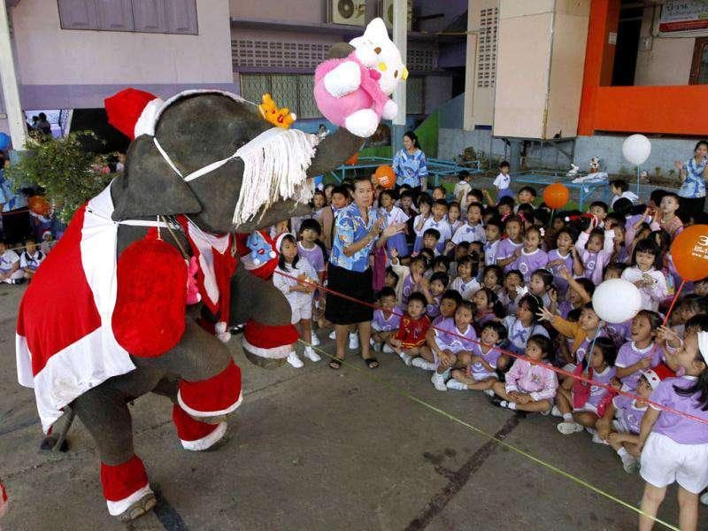 An elephant dressed as Santa Claus distributes a stuffed toy to students during Christmas celebrations at Jirasart school in Ayutthaya, 70 km (44 miles) north of Bangkok. Reuters/Sukree Sukplang