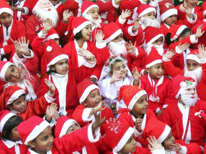 Children dressed in Santa Claus costumes wave while singing Jingle Bells during Christmas celebrations at their school in the northern Indian city of Chandigarh. Reuters/Ajay Verma