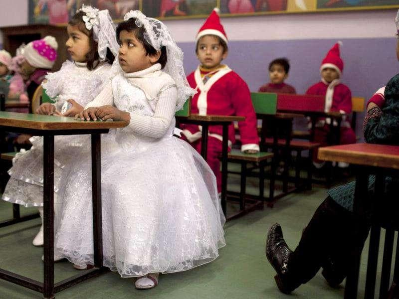 Children dressed in festive clothing sit in a class at a kindergarten on the last day before school holidays in New Delhi. AP Photo/Kevin Frayer