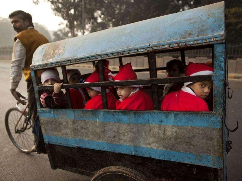 Children wearing festive clothing ride in the back of a bicycle rickshaw on their way to a Christmas party at a kindergarten on the last day before school holidays in New Delhi. AP Photo/Kevin Frayer