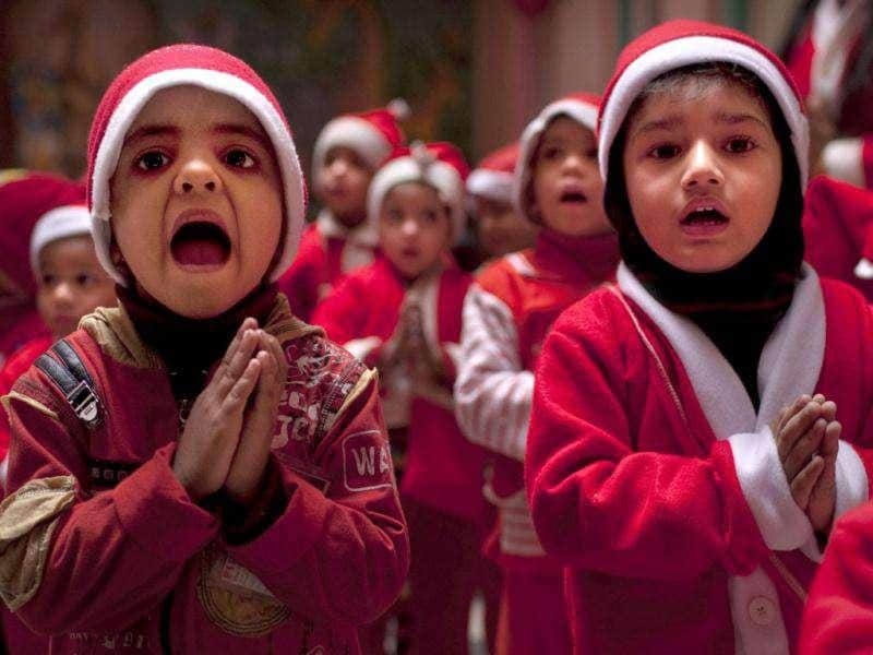 Children dressed in festive clothing sing during a Christmas party at a kindergarten on the last day before school holidays in New Delhi. AP Photo/Kevin Frayer