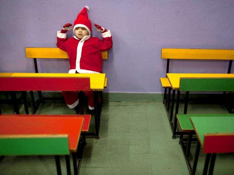 A boy dressed in festive wear as he sits in a classroom during a Christmas party at a kindergarten on the last day before school holidays in New Delhi. AP Photo/Kevin Frayer