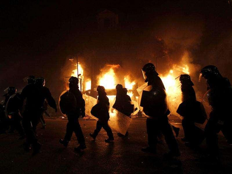 Police officers wearing riot gear walk past a burning building in Tottenham. What started as a protest against killing of a civilian by police, soon turned into suffered widespread rioting, looting and arson in London and around. Reuters