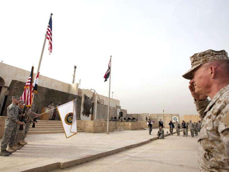 US Marine salutes colour guard lowering flag of US Forces in Iraq during ceremony for US military to retire flag signifying end of their presence in Iraq at Baghdad Diplomatic Support Center. Reuters