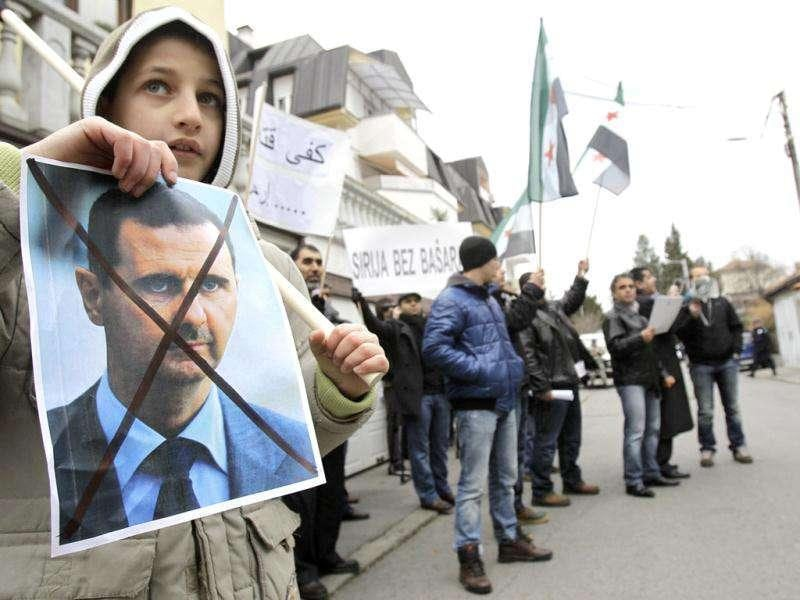 A boy holds a crossed out picture of Syrian President Bashar al-Assad during a rally against his regime in front of the Syrian embassy in Belgrade, Serbia.