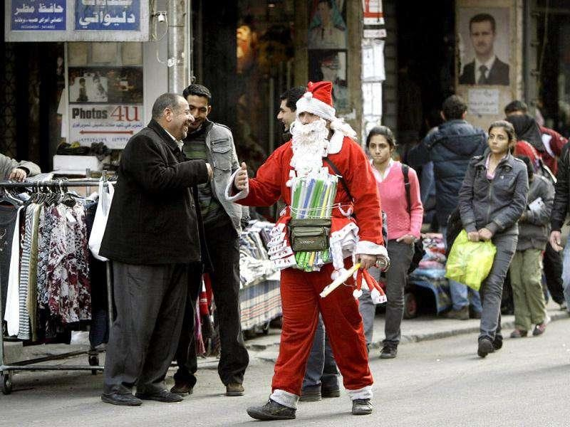 A Syrian vendor, dressed as a Santa Claus walks past a portrait of President Bashar al-Assad at a Christian dominated neighbourhood.