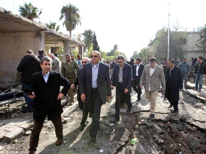 Deputy Arab League Seretary General Samir Seif al-Yazal (2nd L) inspects with a group of Arab observers the site of a suicide attack, which targeted the Syrian General Intelligence headquarters, in Damascus.