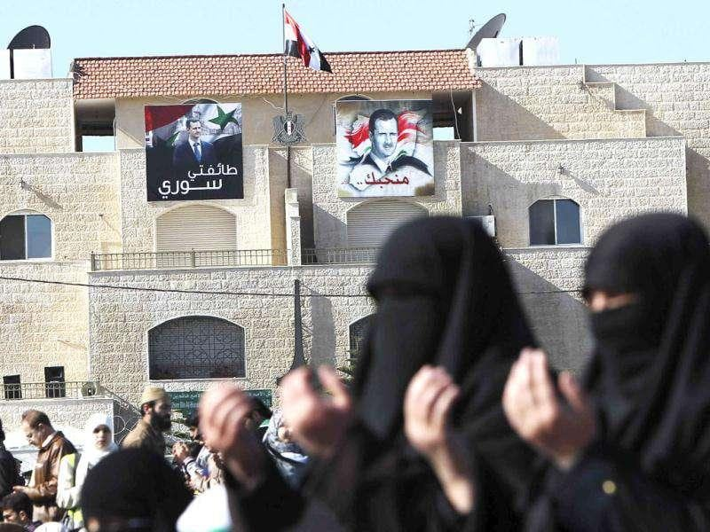 Posters of Syrian President Bashar al-Assad are seen in the background as Syrians living in Jordan perform Friday prayers before staging a protest against him, in front of the Syrian embassy in Amman.