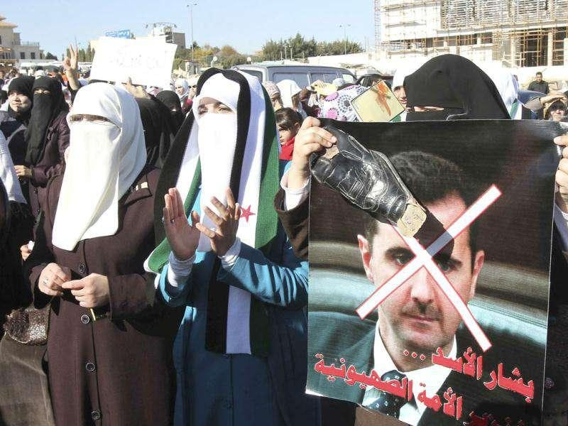 Syrians living in Jordan hold a shoe against a poster of Syrian President Bashar al-Assad as they shout slogans during a demonstration, after Friday prayers in front of the Syrian embassy in Amman.