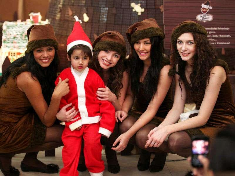 Foreigners girls dressed as chocolate Santa Claus, distributing gifts and chocolates among children during Christmas festivities at Select City mall l in Saket in new Delhi on Friday. Ht photo
