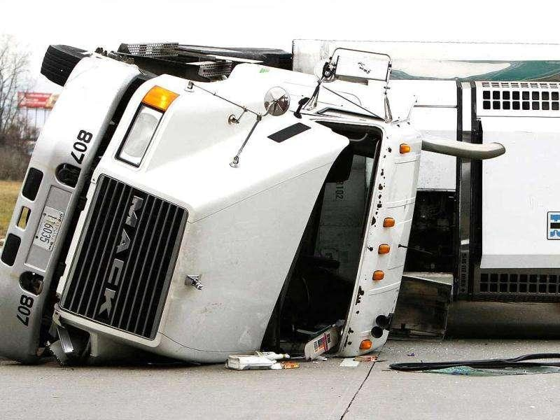 An overturned semitrailer carrying a load of Edy's ice cream is seen on Interstate 69 down, in Fort Wayne, Ind. Police said 40,000 pounds of ice cream spilled from a truck closing two lanes of southbound I-69 at the start of the holiday weekend. AP Photo/The Journal-Gazette, Michelle Davies