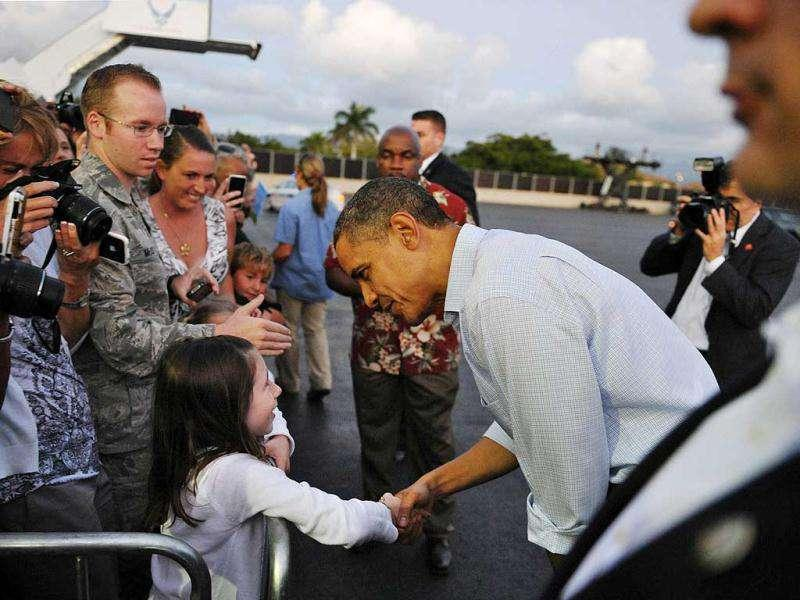US President Barack Obama greets a young wellwisher upon arrival at Hickam Air Force Base in Honolulu, Hawaii. Obama was beginning his delayed vacation after Congress passed a 2-month payroll tax extension. AFP Photo/Mandel Ngan