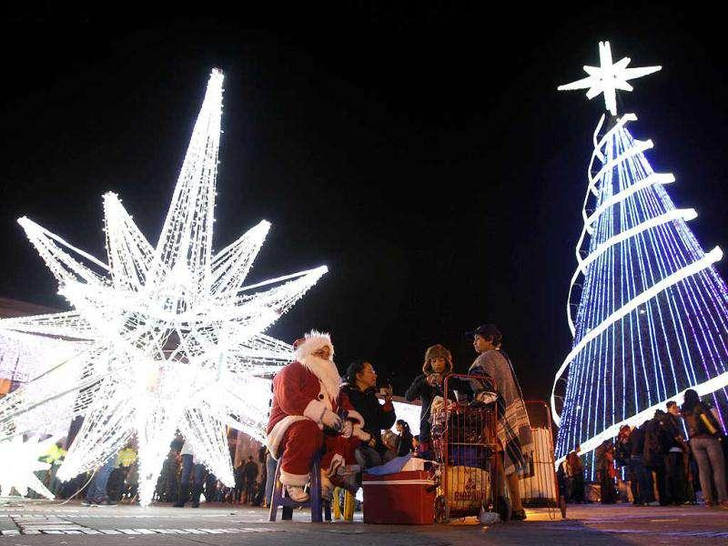 A woman dressed as Santa Claus sits next to a Christmas three and a Christmas Star at Bolivar square in Bogota, Colombia. AP Photo/Fernando Vergara