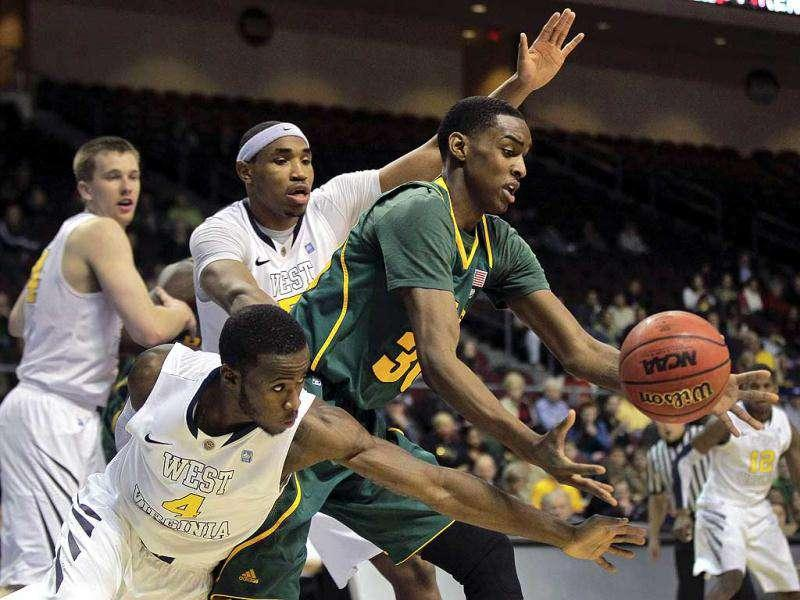 Baylor's Quincy Miller, center, scrambles for a loose ball against West Virginia's Jabarie Hinds, rear, and Kevin Jones (4) in the second half of an NCAA college basketball game in Las Vegas. AP Photo/Julie Jacobson