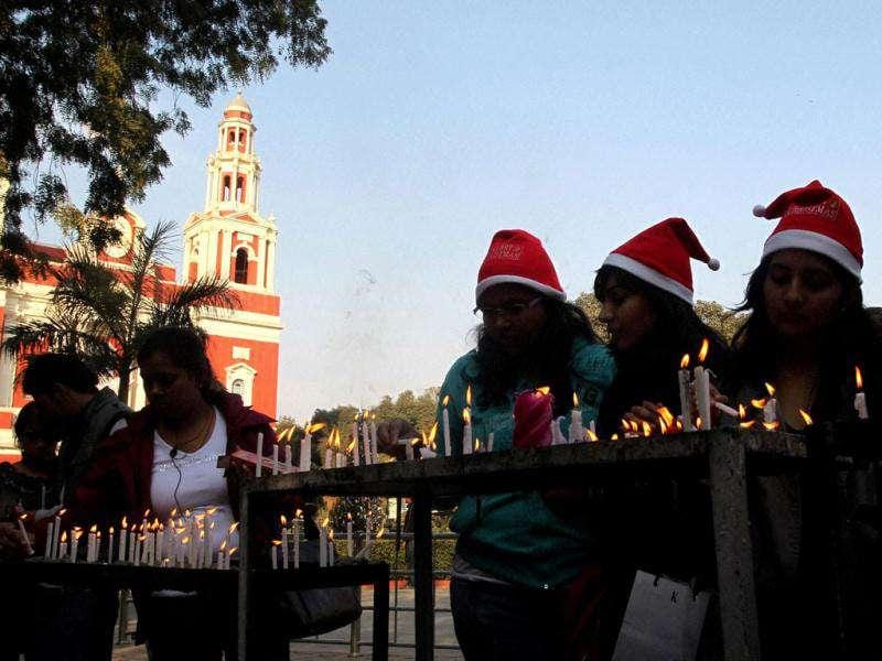 People light candles at Sacred Heart Cathedral on the eve of Christmas festival in New Delhi.