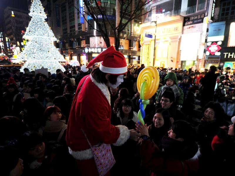 A South Korean man dressed as Santa Claus gives out balloons to people in front of a Christmas tree in Seoul.