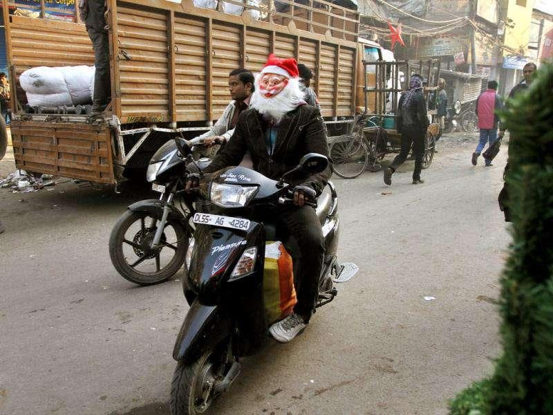A man wearing a Santa Claus mask rides a scooter in New Delhi.