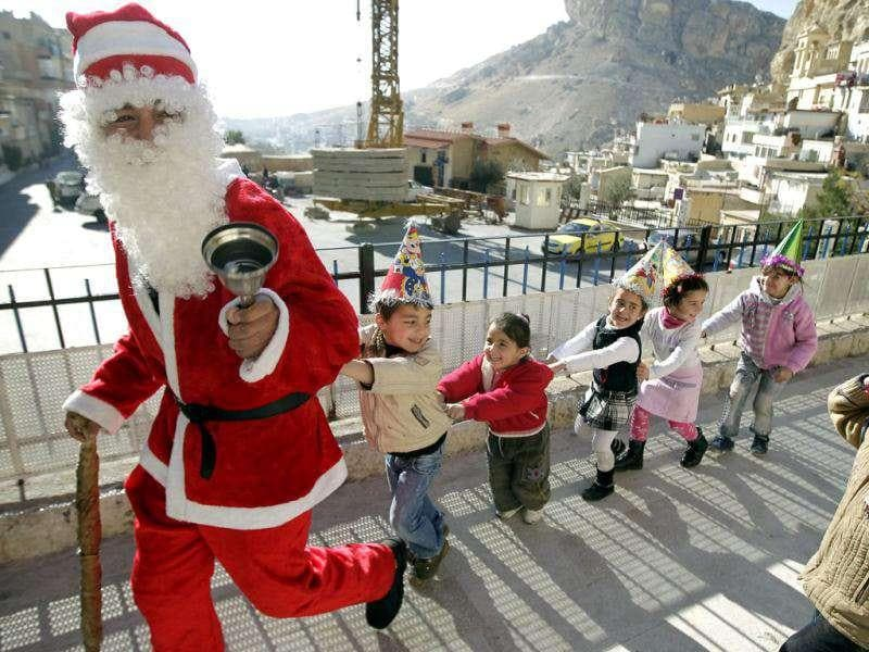 A Syrian man dressed as Santa Claus plays with orphans during a Christmas celebration at the Mar Takla monastery in the Christian village of Maalula.