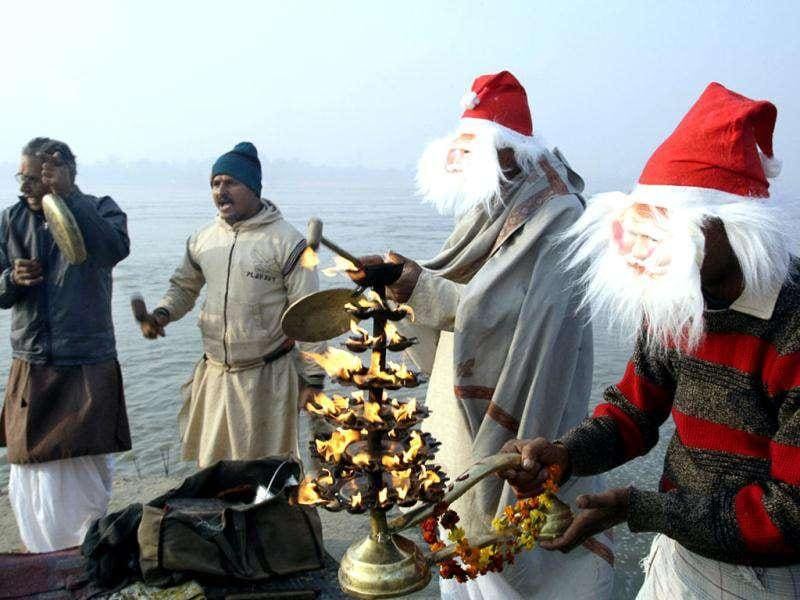 Men wearing Santa Claus masks offer prayers after taking a holy dip in the Sangam, confluence of three rivers, the Ganga, the Yamuna and Saraswati on the occassion of Christmas in Allahabad.