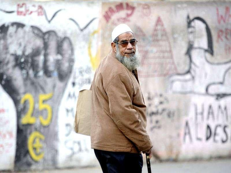 An Egyptian man walks past political graffiti painted on a wall along a road leading to Cairo's Tahrir Square. AFP Photo/Filippo Monteforte