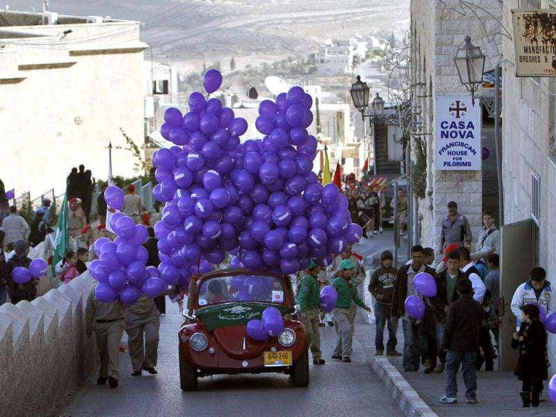 A car loaded with balloons to be given to residents as part of the Christmas celebrations near The Church of the Nativity in West Bank town of Bethlehem. Reuters/Mohamad Torokman