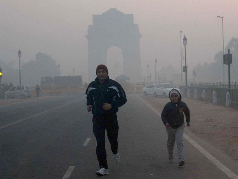 A young girl jogging with her father near India Gate in New Delhi braving the cold on a chilly morning.