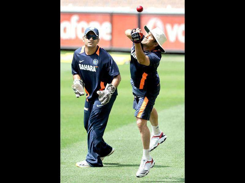 Sachin Tendulkar (R) attempts to take a catch as captain MS Dhoni (L) looks on during training for their upcoming Test match against Australia at the Melbourne Cricket Ground. AFP Photo/William West