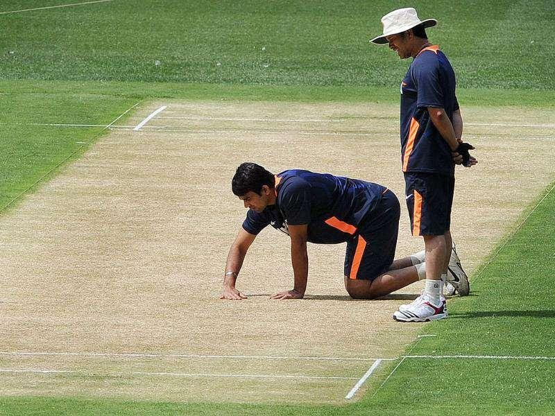 Sachin Tendulkar (R) and teammate Zaheer Khan (L) inspect the wicket at the Melbourne Cricket Ground. AFP Photo/William West
