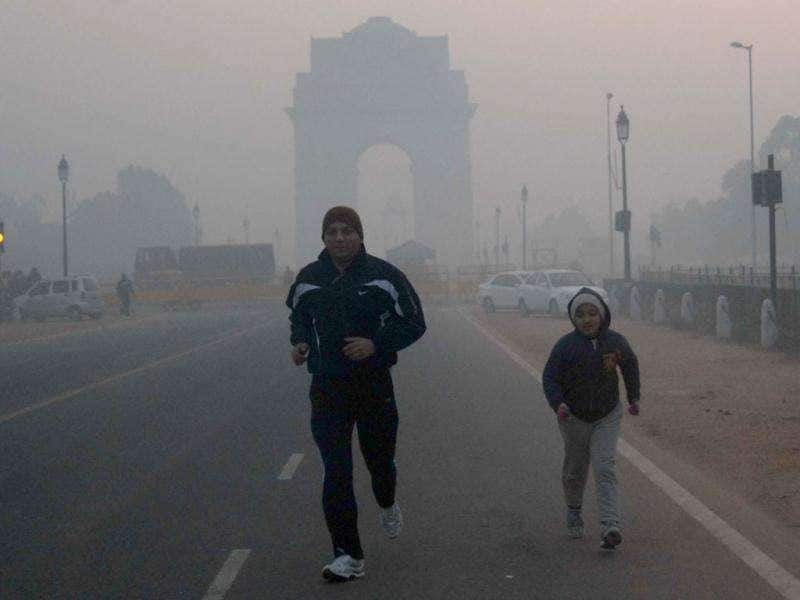 A young girl jogs with her father near India Gate in New Delhi, braving the cold on the city's coldest Christmas in five years.