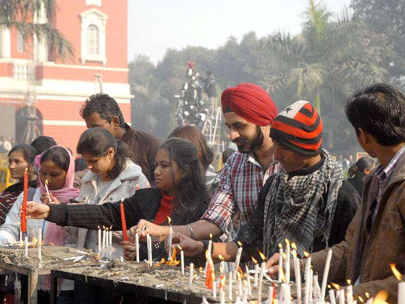 Devotees light candles at a church on the occasion of Christmas in New Delhi.