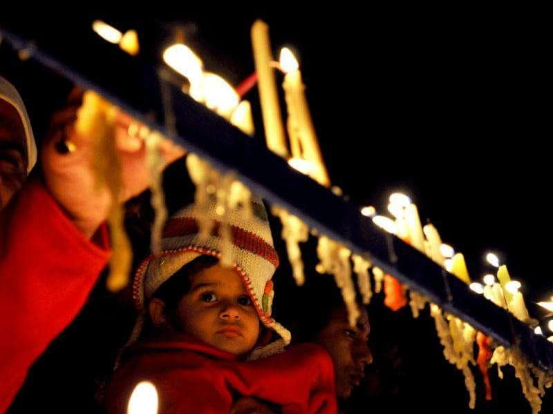 A child looks at candles lit by people offering prayers at the Sacred Heart Cathedral on Christmas in New Delhi.