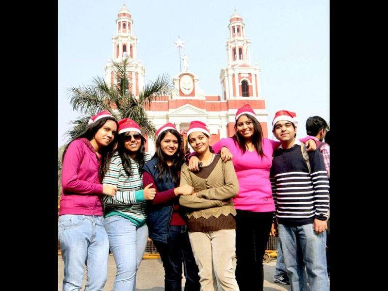 Young girls pose with a boy outside a church on the occasion of Christmas in New Delhi.