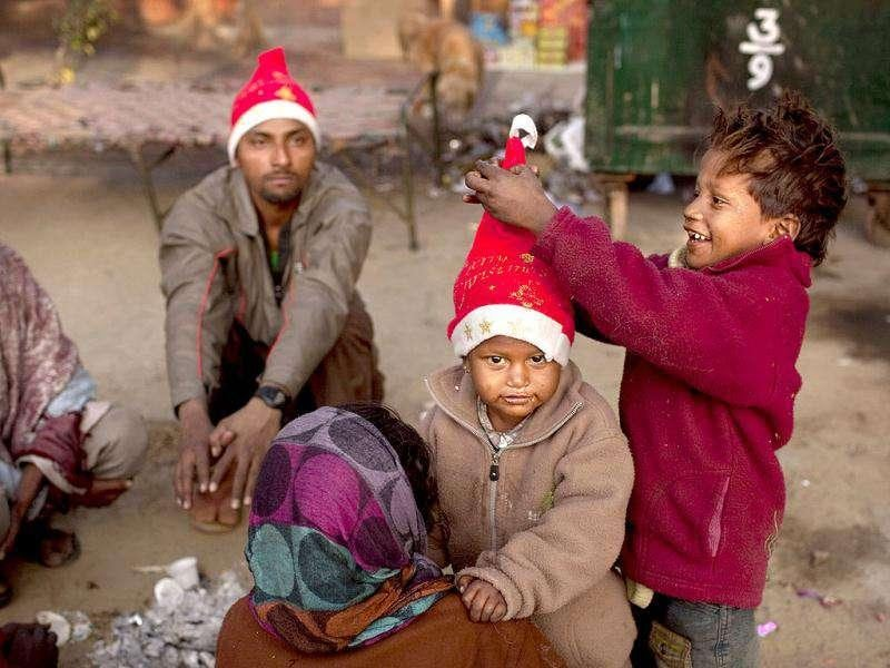 A boy adjusts a festive hat on another as they sit around a fire with their parents who are homeless street vendors at a Christmas market near the Sacred Heart's Cathedral in New Delhi.