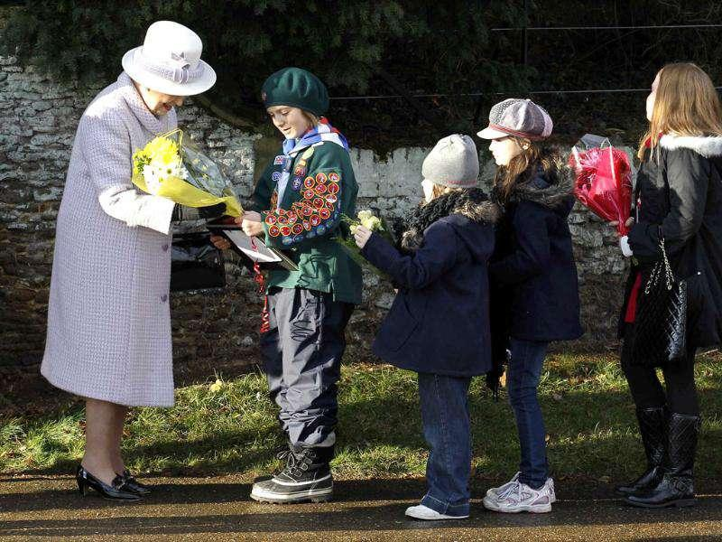 Britain's Queen Elizabeth accepts flowers from children as she leaves a Christmas Day service at St Mary Magdalene Church on the Royal estate at Sandringham, Norfolk in east England. Reuters/Suzanne Plunkett