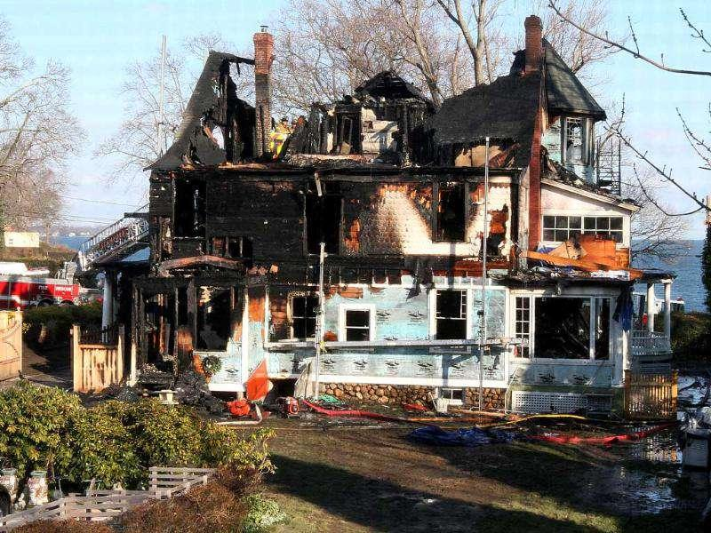 Firefighters investigate a house where an early morning fire left five people dead in Stamford, Connecticut. AP Photo